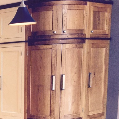 Fully bespoke shaker style fitted kitchen hand built from solid wood featuring curved cupboard.